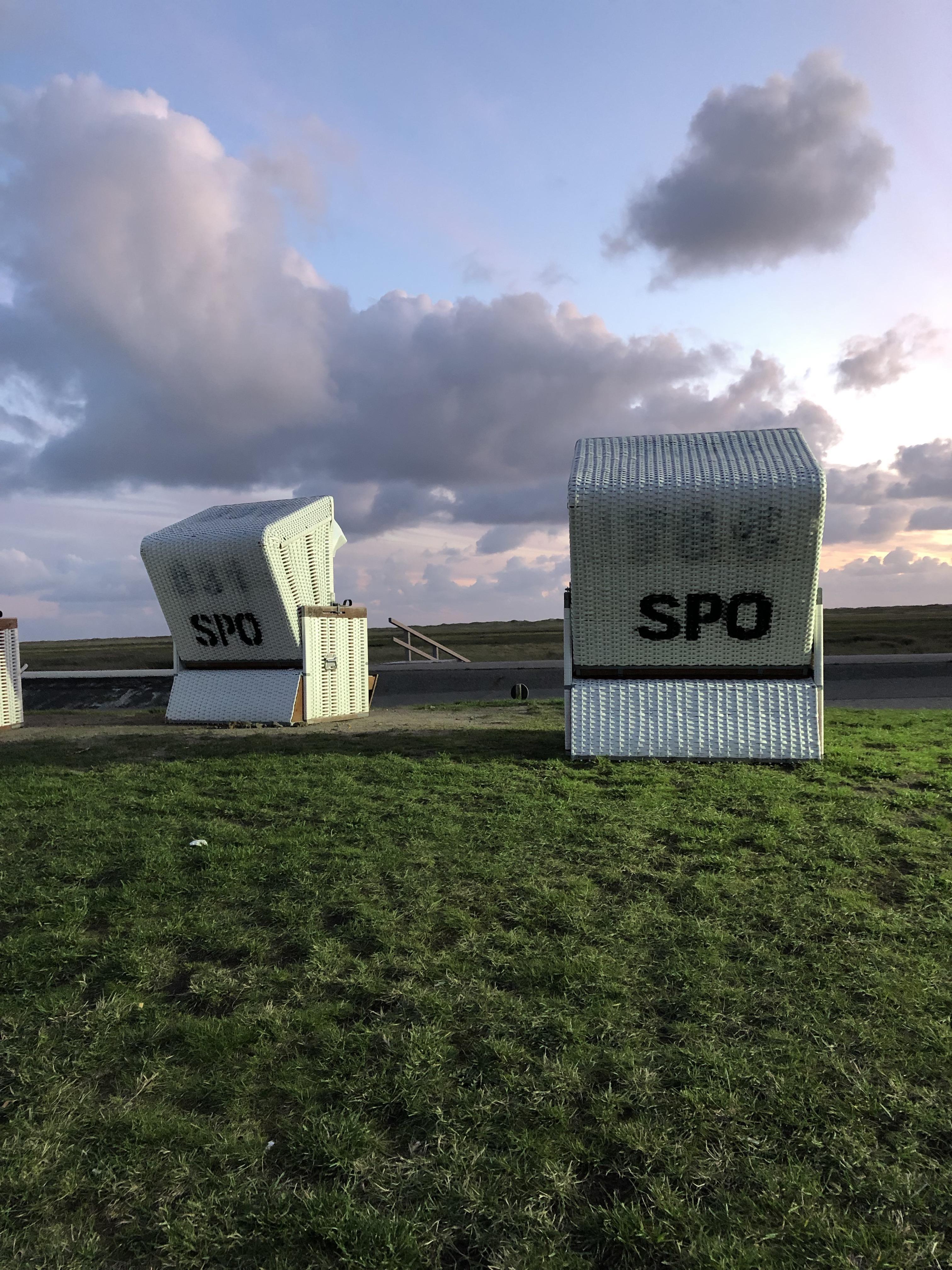 """Zwei Strandkörbe mit der Aufschrift """"SPO"""" auf einer Wiese, Abendhimmel mit Wolken"""